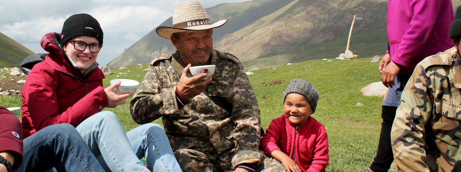 A student sits outside with a local family in Kyrgyzstan and enjoys a cup of sour milk.