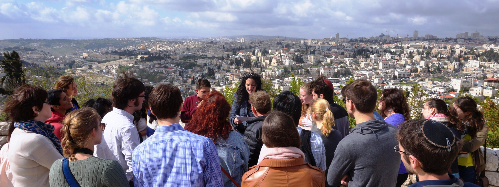 Students listen to a tour guide while looking over the city.