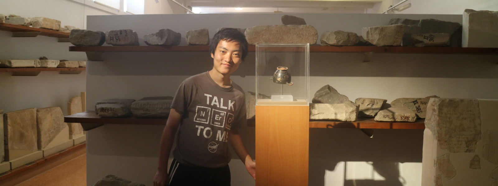 The student is standing next to a display case and there are shelves of artifacts behind him.