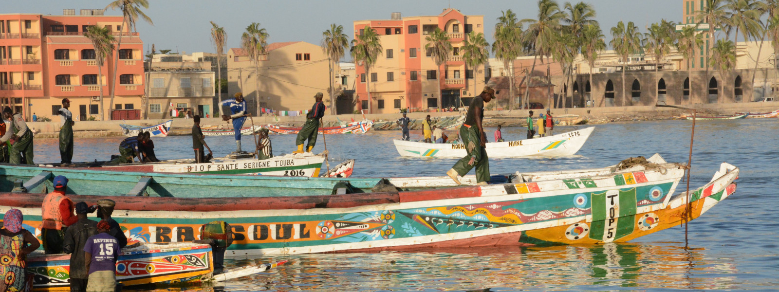 People are walking on and standing beside brightly painted boats by the shore.