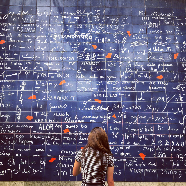 """A student faces a tile wall that features the words """"I love you"""" written in many different languages."""