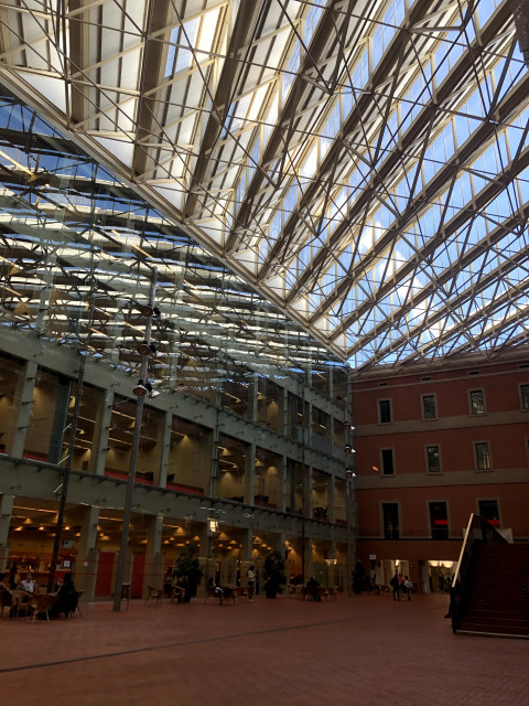 A view from inside a building on the UPF campus, with its dramatic glass ceiling.