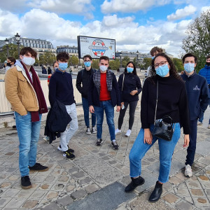 A group of students wearing face masks stand together by the bank of the Seine.