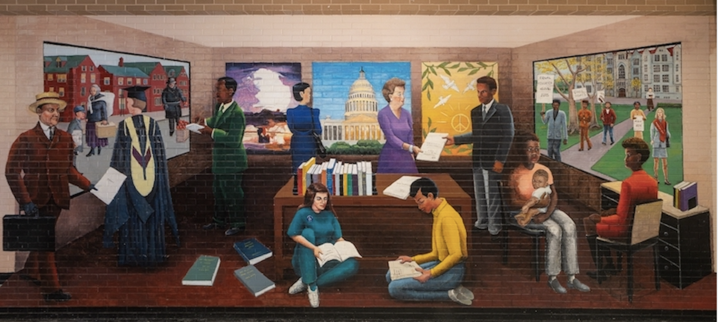Mural by artist Astrid Fuller from the University of Chicago Office of Civic Engagement. Mural depicts various groups of people reading and talking in a library setting.