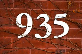 Photo of white large numbers 935 on a brick building with vines - cropped to just the numbers.