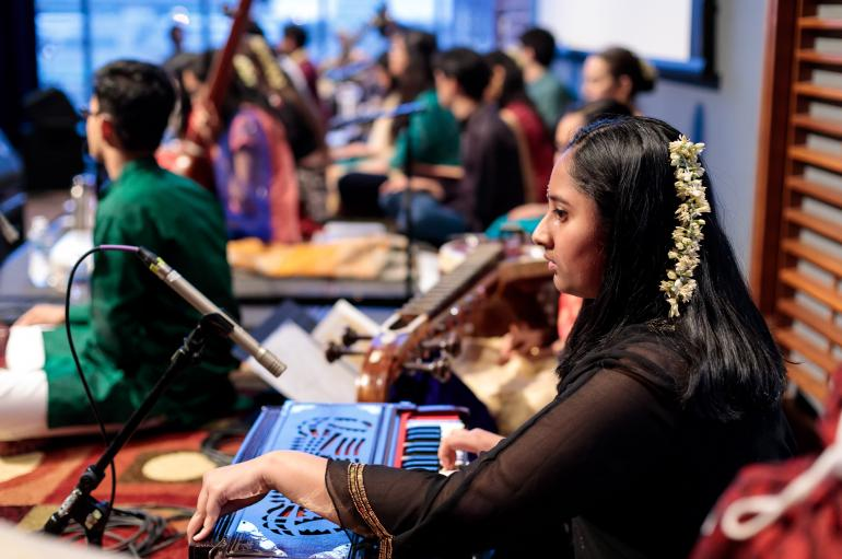A young woman sits at a South Asian instrument wearing colorful clothing