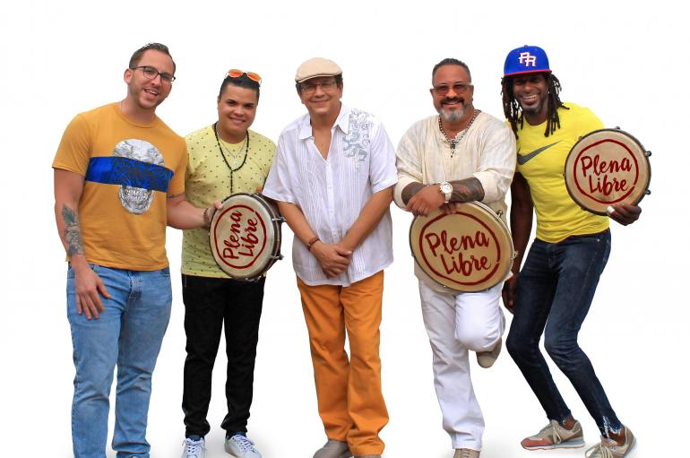 The members of Plena Libre wearing colorful clothing