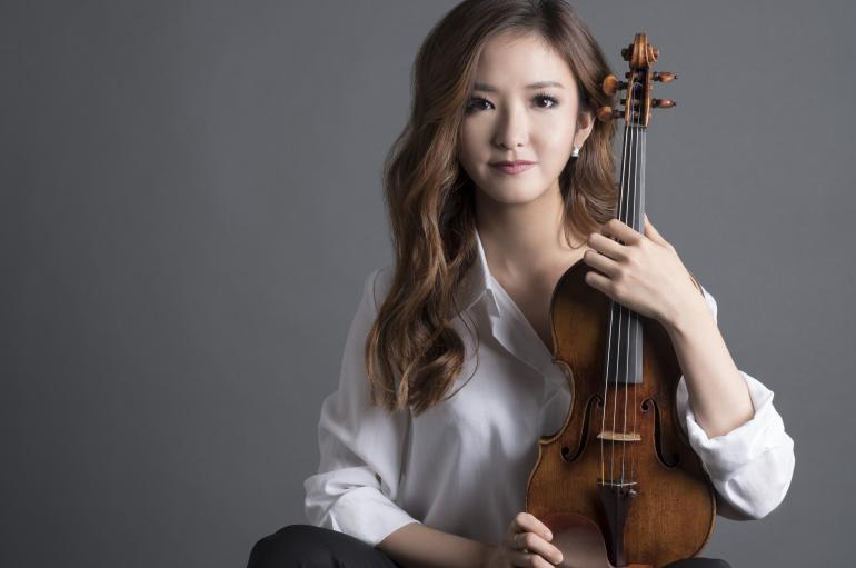 Yoojin Jang holding her violin in front of a gray background