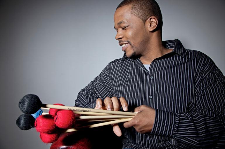 Warren Wolf holding a bundle of vibraphone mallets