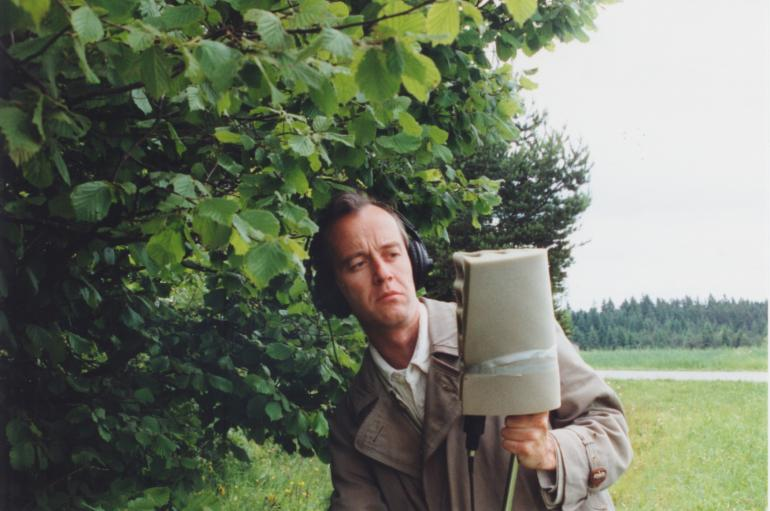 Peter Aberlinger holding a large microphone in a field