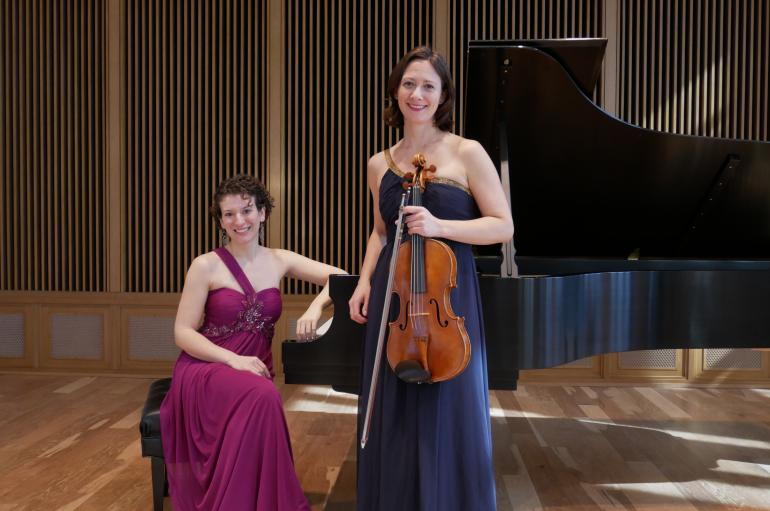 Clare Longendyke wearing a purple dress and sitting at a piano next to Rose Wollman in a blue dress and holding a viola