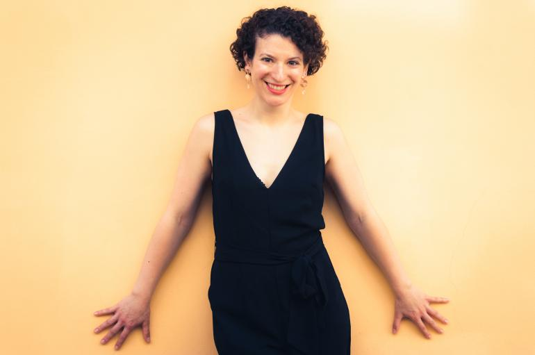 Clare Longendyke with arms outspread in front of a yellow wall
