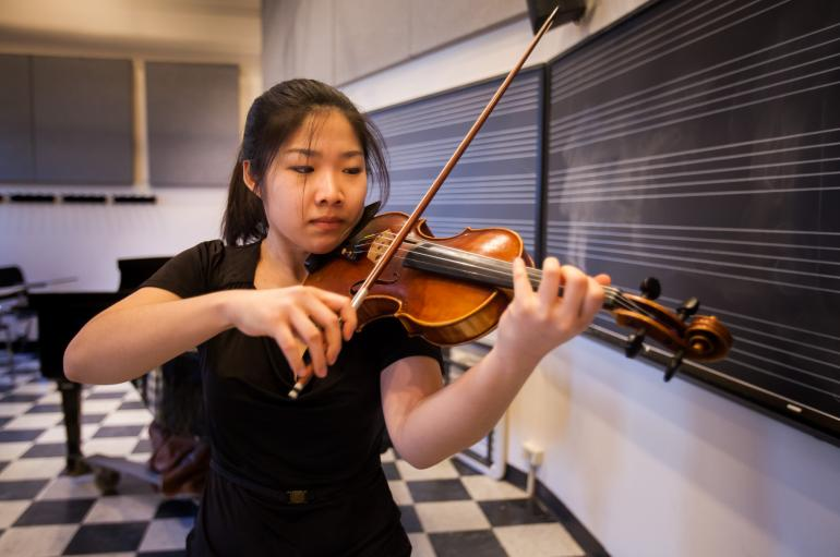 A student practices violin in front of a black board with white staff lines and a grand piano