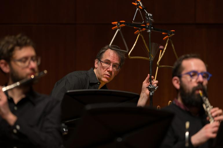 Closeup photo of three men, Tim Munro playing flute, Greg Beyer playing percussion, and Andrew Nogal playing oboe
