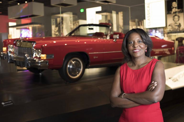 Dwandalyn R. Reece, a black woman wearing a read dress, stands in front of a red vintage hot rod