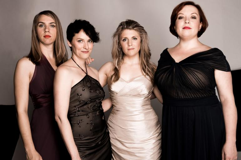 Quince vocal ensemble: 4 women standing next to each other wearing elegant gowns
