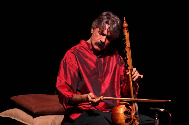 Kayhan Kalhor wearing a red silk shirt while playing a kamancheh