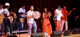 Plena Libre singing and dancing on stage with drums and hand percussion