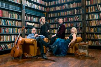 Spektral Quartet sitting in armchairs with instruments in a library