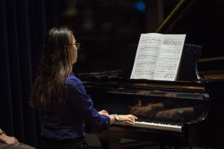 Photo from behind of a young woman playing the piano