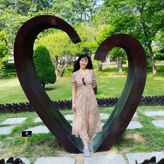 Tricia Park in front of a heart sculpture in Korea