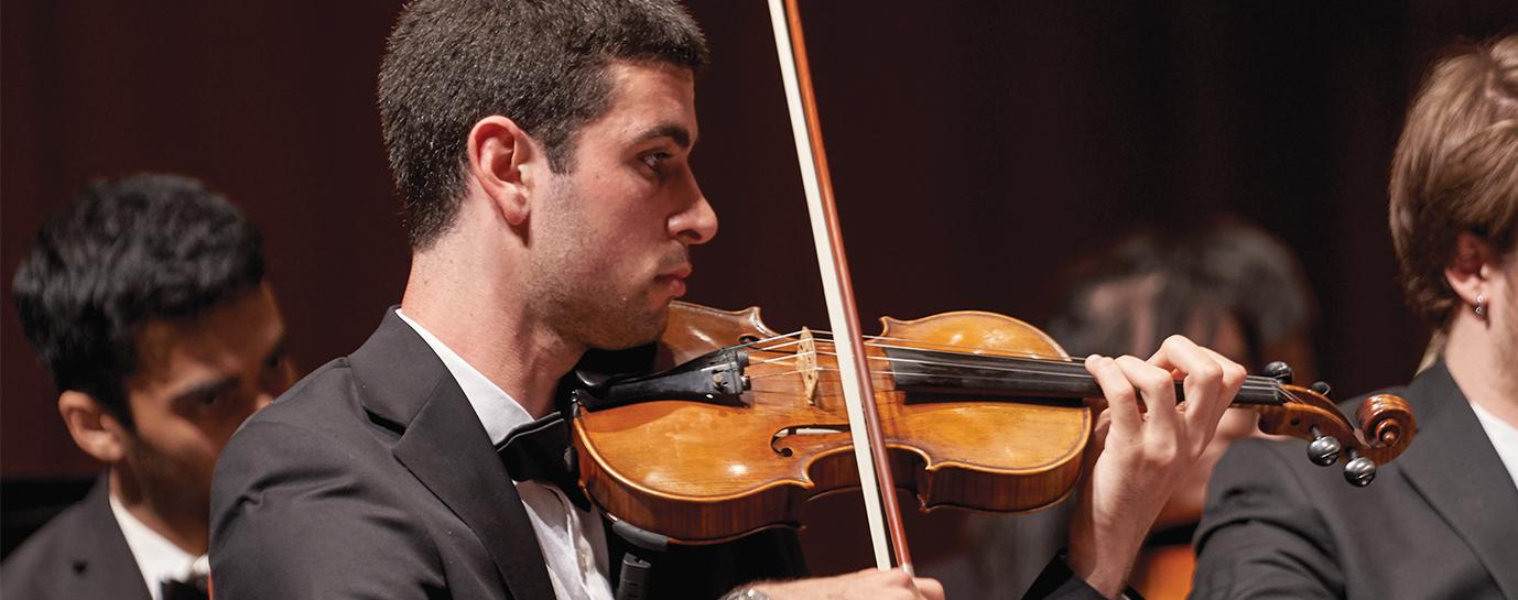 Closeup photo of a man in the University of Chicago Symphony Orchestra playing violin in concert, wearing a tux