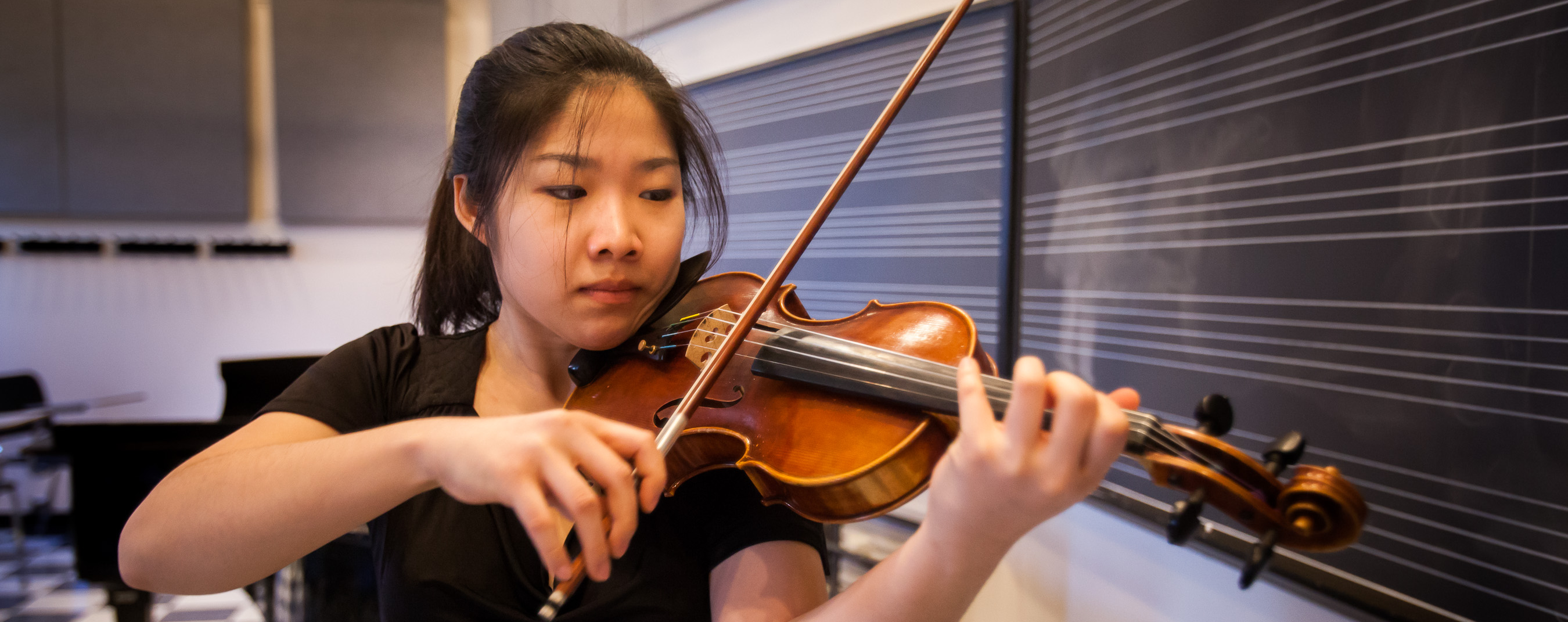 A young woman practices violin in front of a black board with white staff lines and a grand piano