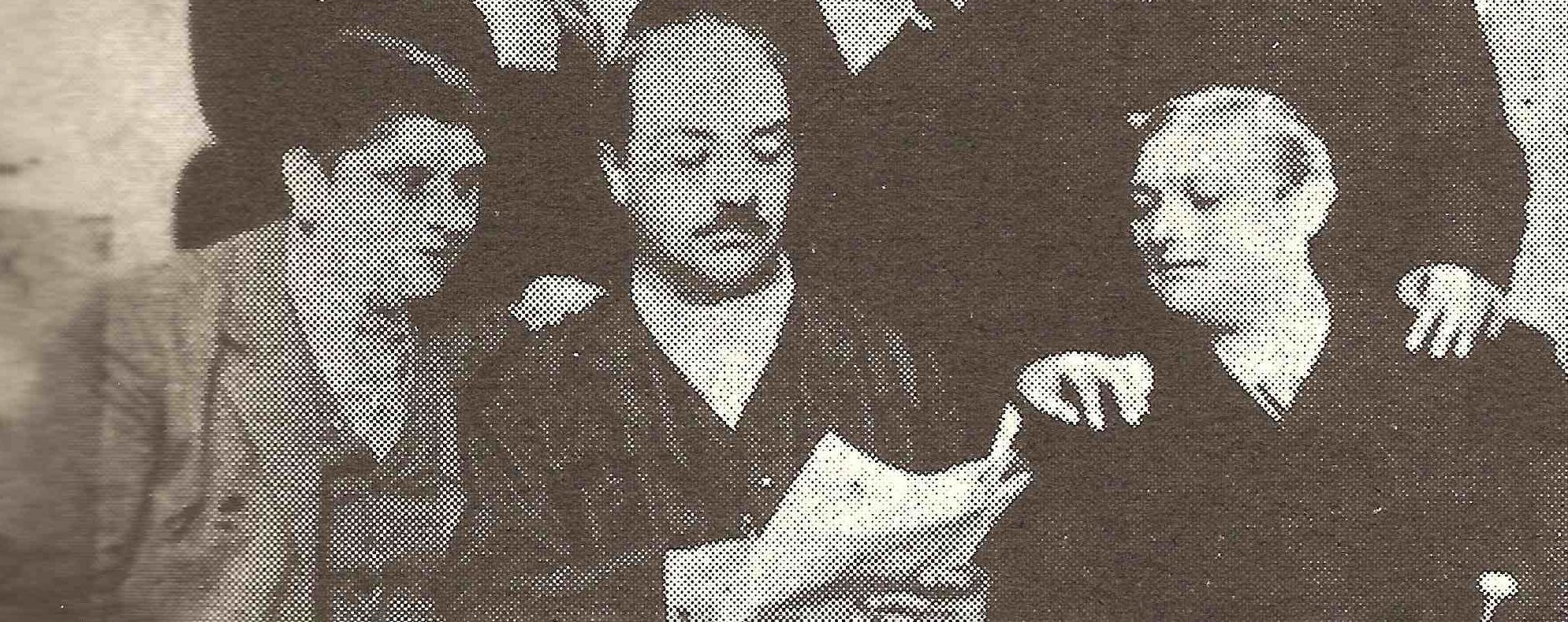Sepia toned photo showing three men around a newspaper in the late 1800s. The two men without mustaches are castrati: Alessandro Moreschi on the left and Giovanni Cesari on the right