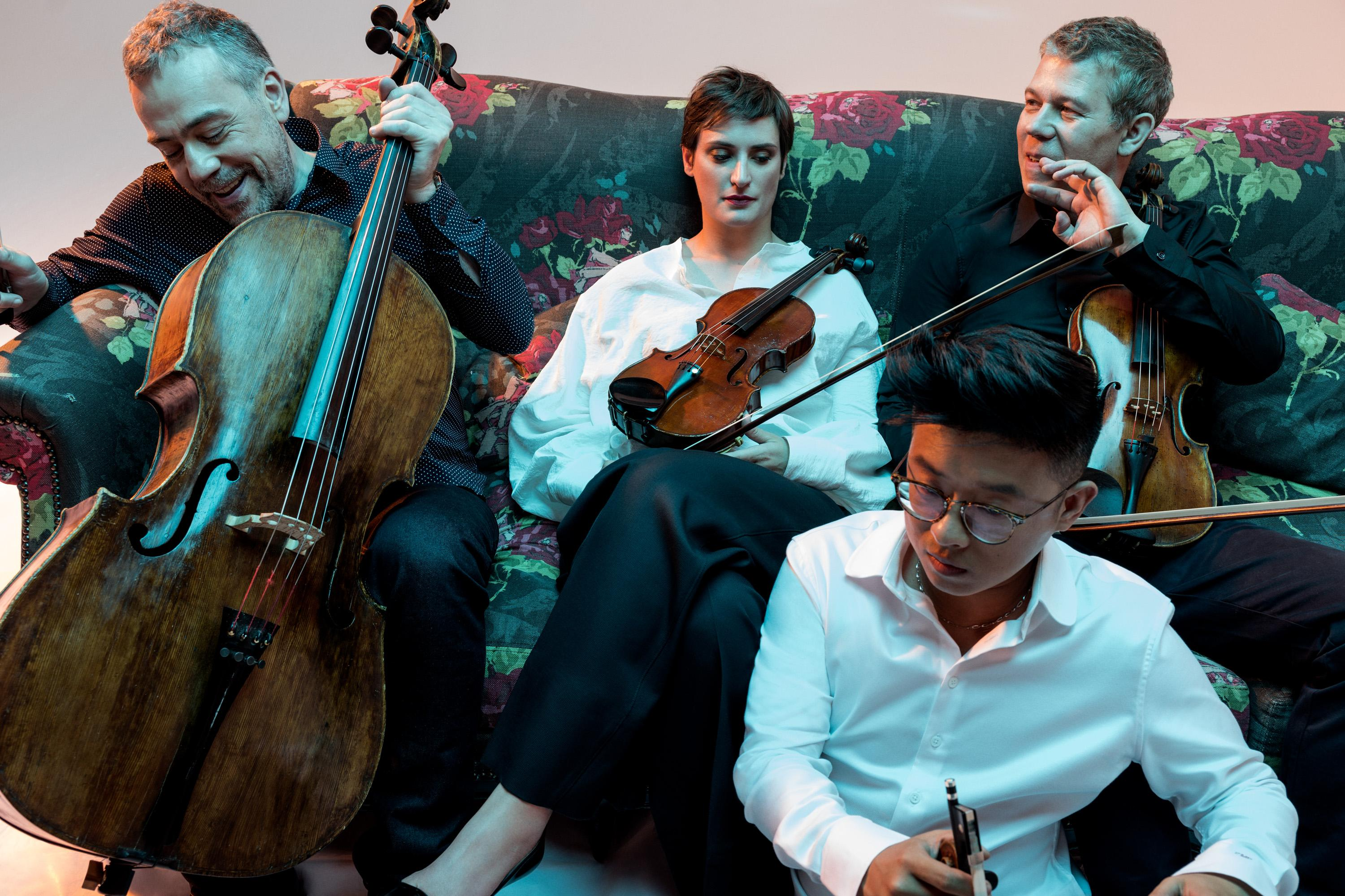 members of Quatuor Diotima posing on a couch with their instruments