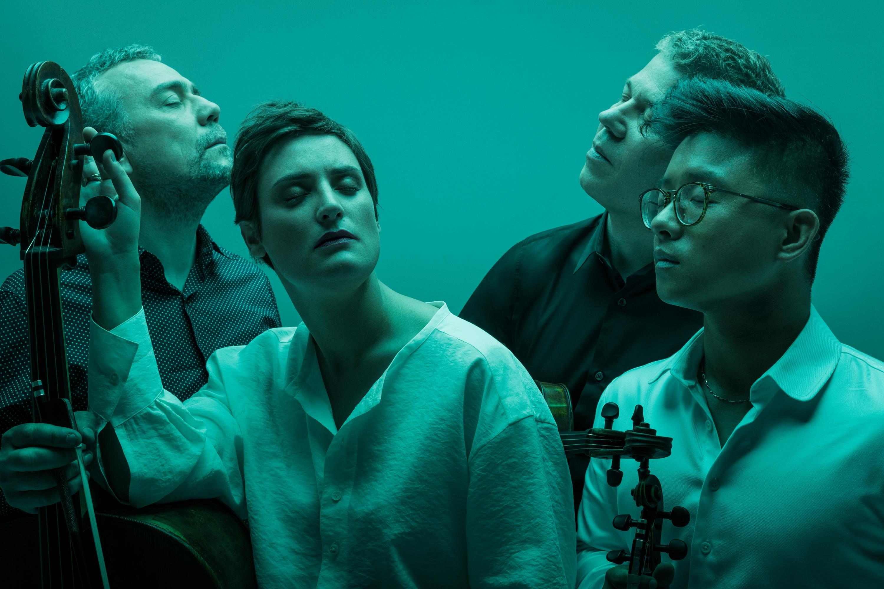 members of Quatuor Diotima posing with their instruments in blue-green lighting