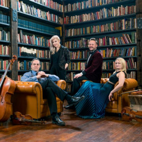 Spektral Quartet with instruments surrounded by books in a library
