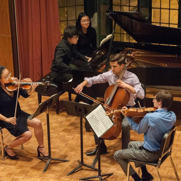 Four students, a violin, viola, and cello player and pianist, are seen from above performing on the Fulton Recital Hall stage