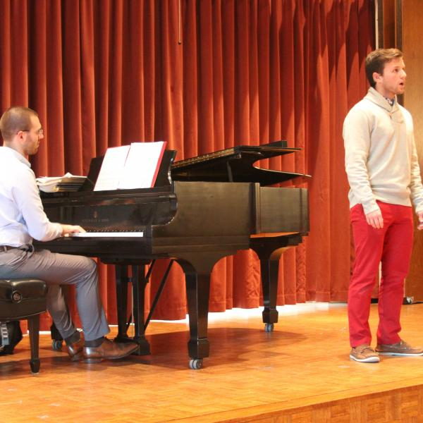 A young man performs with piano on stage in Fulton Recital Hall