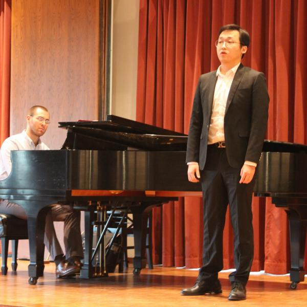 A young man performs on stage with piano in Fulton Recital Hall
