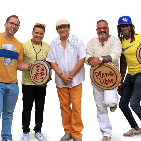 The members of Plena Libre wearing colorful clothing and holding drums