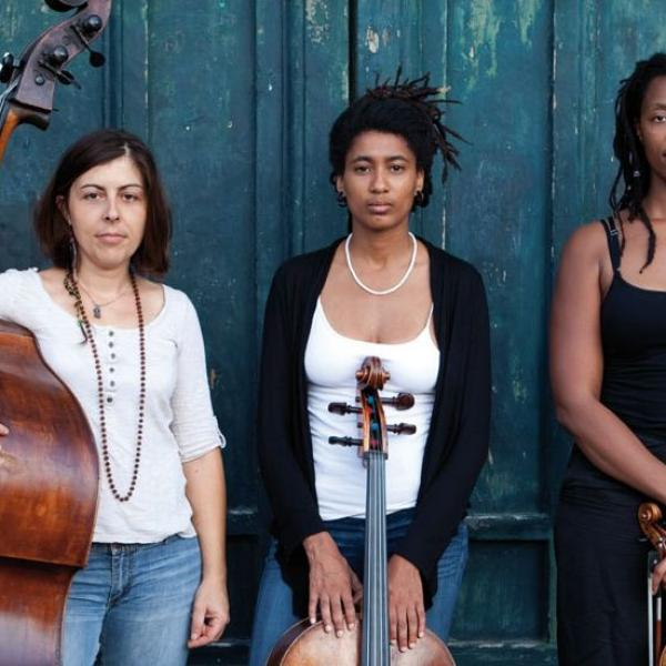 The women of the trio HEAR in NOW stand in front of a teal wall holding their instruments
