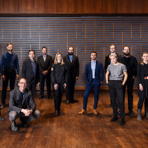 The Grossman Ensemble members standing at various distances in a large room with dark brown walls and wood floors