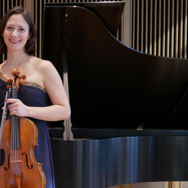 Rose Wollman wearing a blue dress and holding a viola in front of a piano