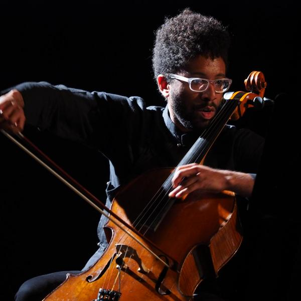 Seth Parker Woods wearing black and playing cello in a dark room, lit from the side