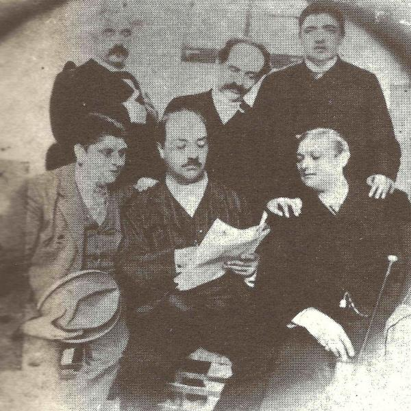 Archive photo showing a group of Italian men sitting around a newspaper in the late 1800s. Alessandro Moreschi is on the bottom left, and Giovanni Cesari is on the bottom right.