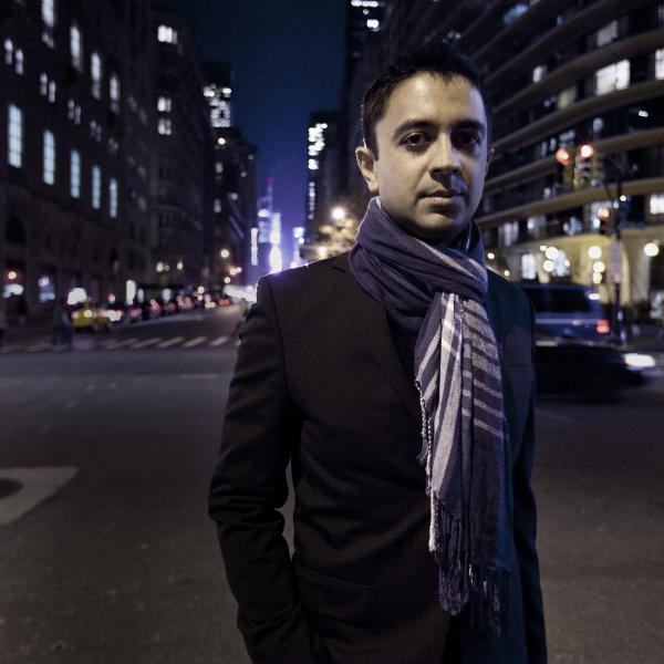Vijay Iyer standards wearing a dark blazer and striped scarf in a dark street in New York
