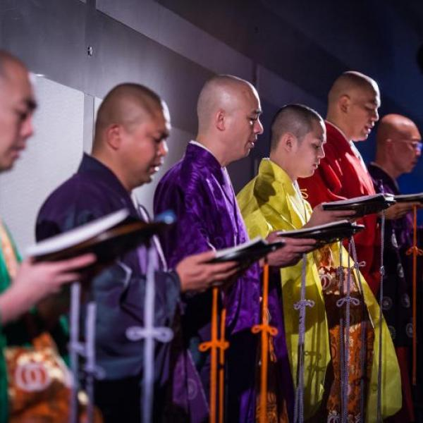 Six monks wearing brightly colored silk robes is shown chanting while holding chant books