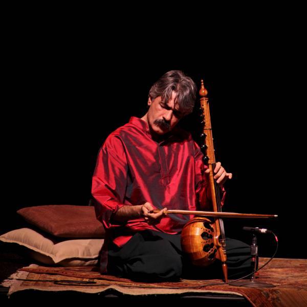 Kayhan Kalhor wearing a red silk shirt while playing a kamancheh