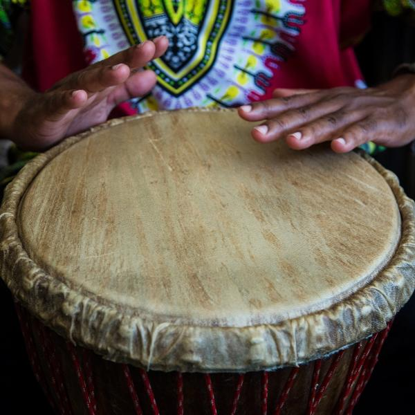 A close-up shot of hands on a drum