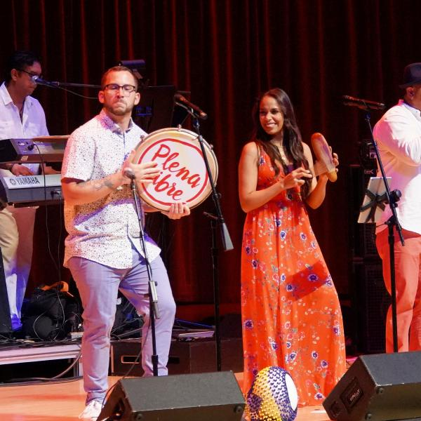 Plena Libre singing and dancing on stage with hand percussion and drums