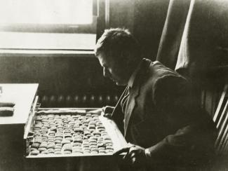 Daniel D. Luckenbill examines cuneiform documents. Mr. Luckenbill, a professor of Assyriology at the University of Chicago, was the first editor of the Chicago Assyrian Dictionary. Photo courtesy of University of Chicago Library, Special Collections Research Center [Image Identifier: apf1-04021].